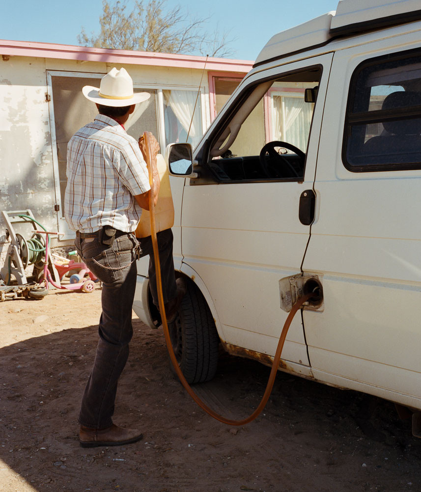 Man filling a van with gas out of a jug in Baja, Mexico