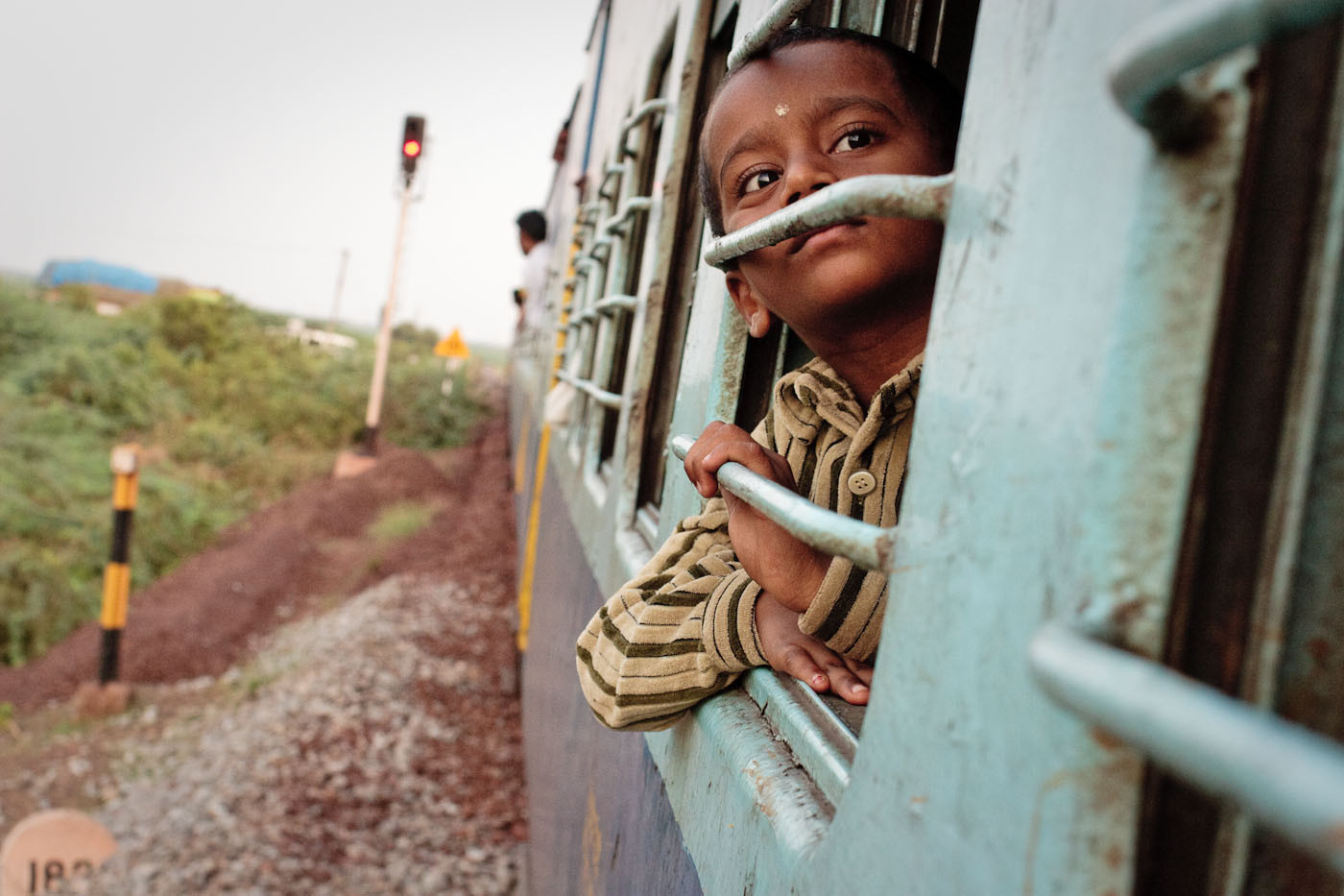 View of the exterior of a train in southern India. A young boy is sticking his head from the window of the sleeper car.
