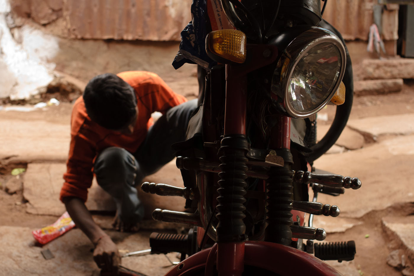 Indian boy fixing a flat tire on a scooter in a bike shop in Hospet, India