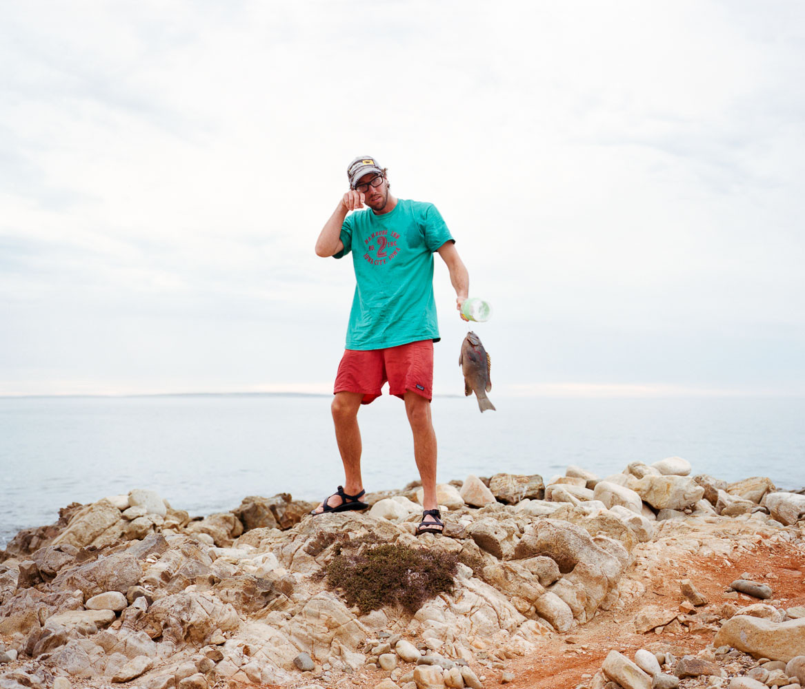 Portrait of a man standing with a fish he caught in Baja, Mexico