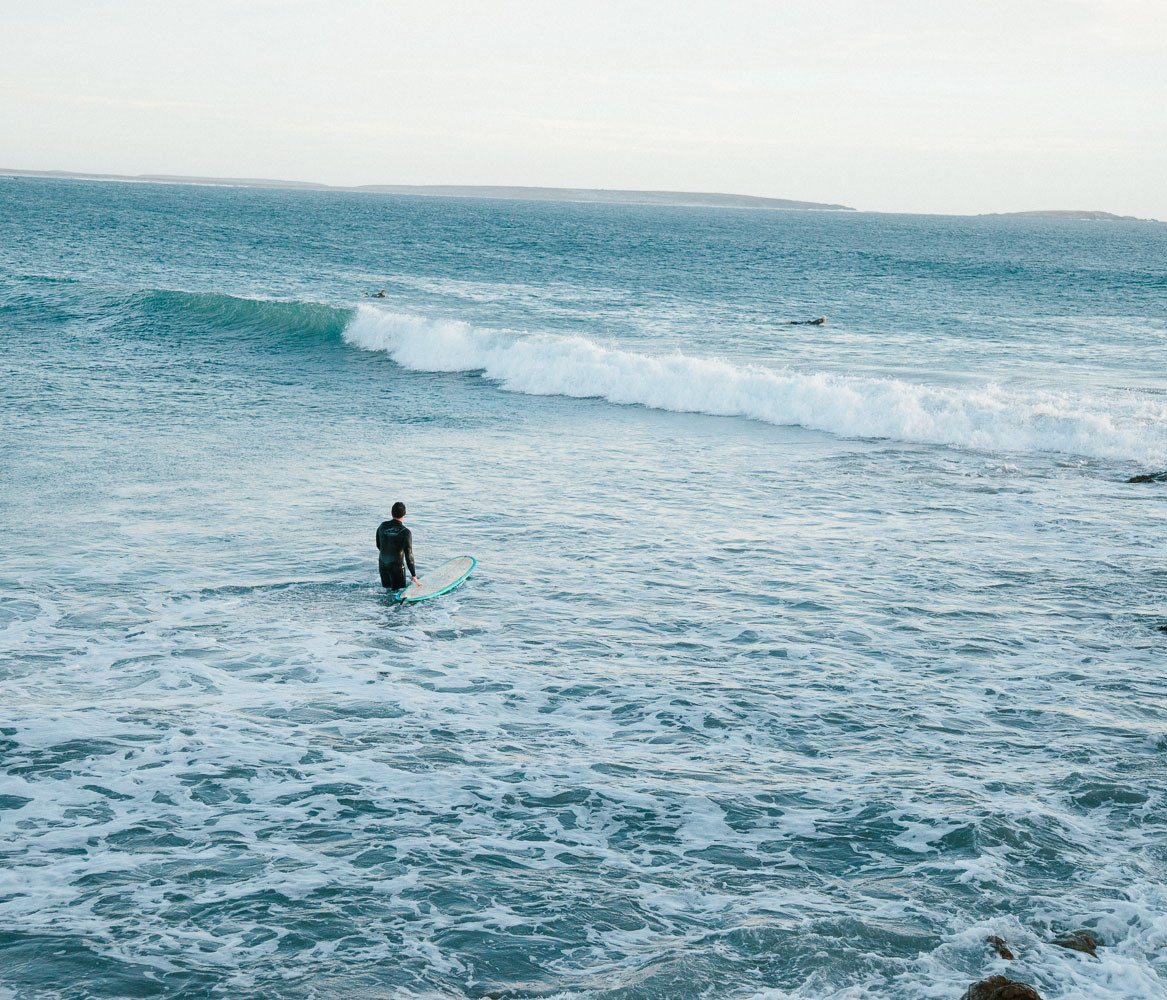 Surfer walking out in Baja, Mexico