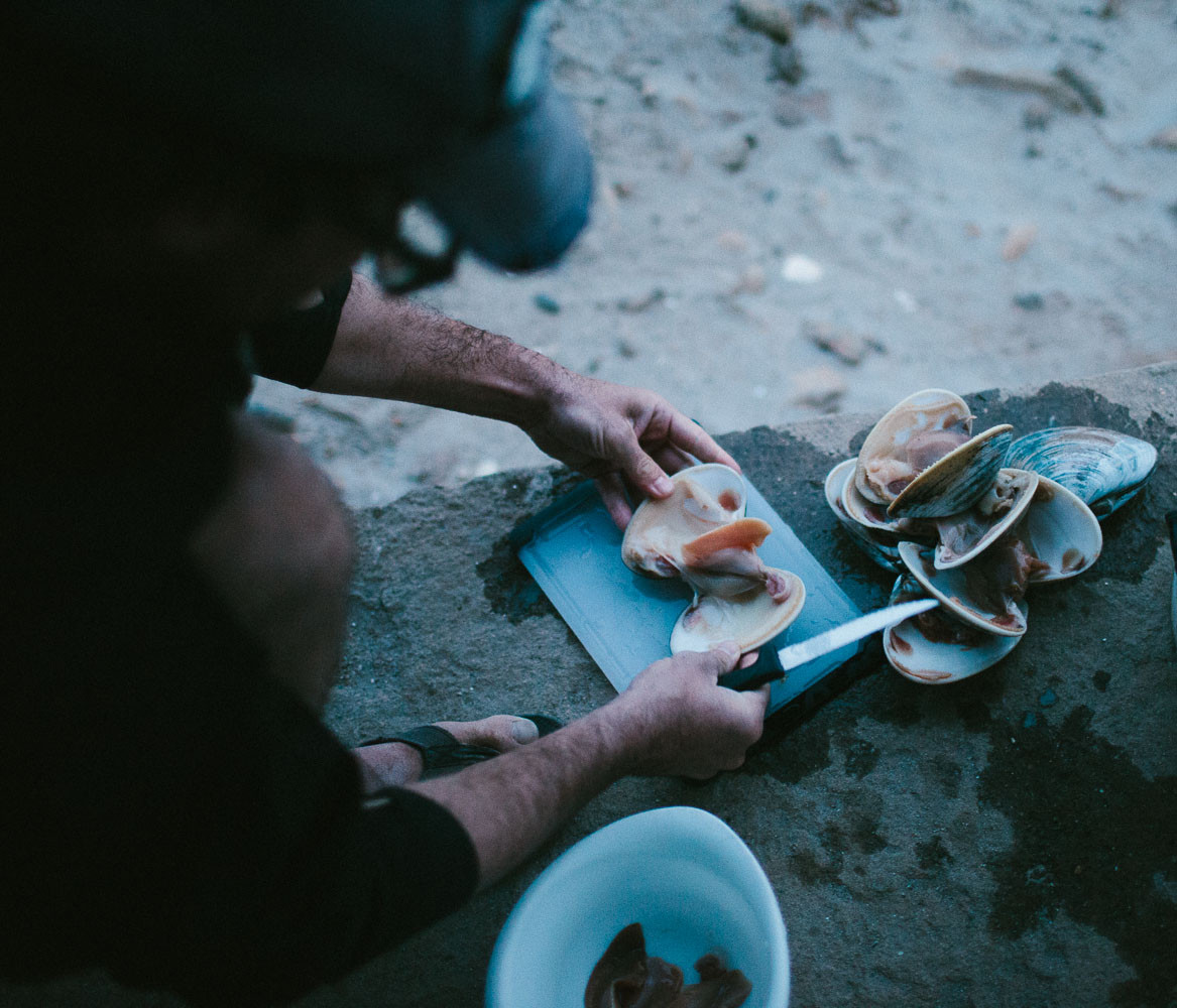 Man cutting up clams on the beach in Baja, Mexico