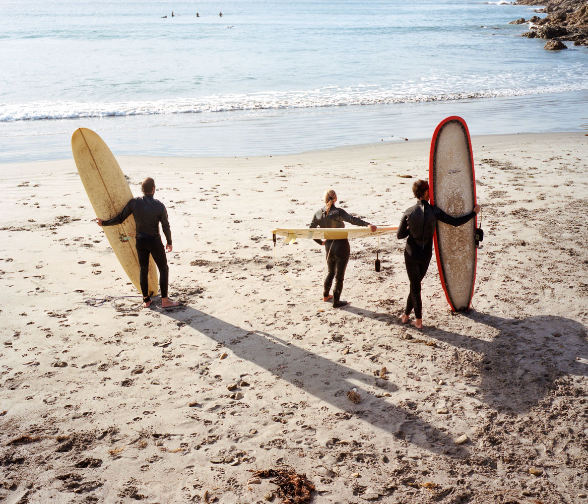 Three surfers on the beach in Baja, Mexico